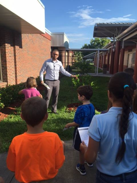 Children at Tanglewood Elementary School's new outdoor classroom enjoy a small lesson from EnSite's Director of Landscape Architecture, Jon Romine